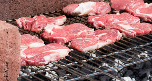 Raw red steaks grilled on barbecue. Detail with grill and embers Stock Images