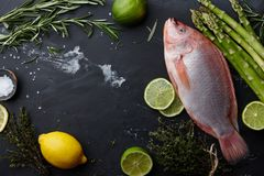 Raw red tilapia fish cooking. With herbs, spices, green asparagus, lemon and lime on black stone background, top view royalty free stock images