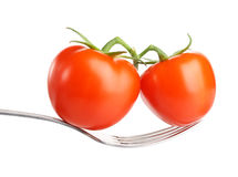 Raw red tomato on fork.  on white Royalty Free Stock Image