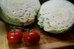 Raw red tomatoes and cut cabbage on wooden cutting board. Two raw red tomatoes and cut cabbage on wooden cutting board on dark background Royalty Free Stock Photography