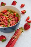 Raw rhubarb strawberry pie ready for cooking in the baking dish on the white kitchen table. Decorated with organic ingredients. Raw rhubarb strawberry pie ready Stock Photography