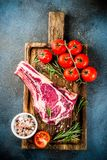 Raw rib eye beef steak. Meat with spices and ingredients for cooking dark rusty background copy space top view royalty free stock photography