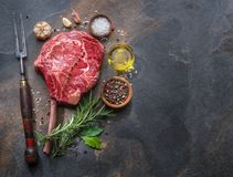 Raw Rib eye steak or beef steak on the graphite board with herbs and spices royalty free stock photo