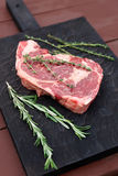 Raw rib-eye steak on cutting board Royalty Free Stock Image