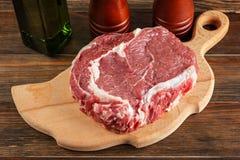 Raw rib-eye steak on a cutting board Royalty Free Stock Photography