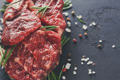 Rib eye steak and spices on wood at black background Royalty Free Stock Images