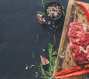 Rib eye steak and spices on wood at black background. Raw rib eye steak with herbs and spices. Cooking ingredients for restaurant dish. Fresh meat, pepper salt Stock Images