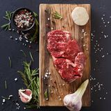 Rib eye steak and spices on wood at black background. Raw rib eye steak with herbs and spices. Cooking ingredients for restaurant dish. Fresh meat, pepper salt Stock Photo