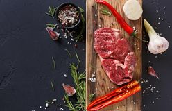 Rib eye steak and spices on wood at black background. Raw rib eye steak with herbs and spices. Cooking ingredients for restaurant dish. Fresh meat, pepper salt Royalty Free Stock Photos
