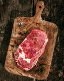 Raw Rib Eye Steak on Rustic Wooden Cutting Board royalty free stock images