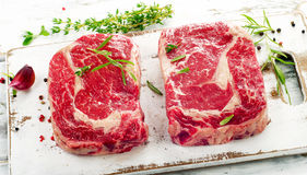 Raw rib eye Steaks  on  a wooden cutting board. Royalty Free Stock Photography