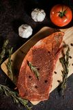 Raw ribey steaks marinated with fresh aromatic herbs, butter and garlic stock photography