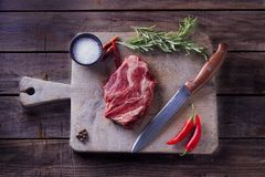 Raw ribeye beef steak With spices for cooking and knife on he cutting board. Top view royalty free stock image