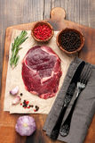 Raw ribeye steak entrecote. Raw ribeye steak on wooden cutting board. top view, vertical Royalty Free Stock Photo