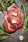 Raw ribeye steak with fresh herbs variety and butter, ingrediets for cooking Royalty Free Stock Photo