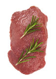 Raw ribeye steak. Garnished with a sprig of rosemary Stock Photo