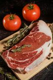 Raw ribeye steak garnished with a sprig of rosemary, garlic and tomatoes. In a black background Stock Image