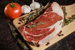 Raw ribeye steak garnished with a sprig of rosemary, garlic and tomatoes. In a black background Royalty Free Stock Photos