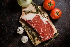 Raw ribeye steak garnished with a sprig of rosemary, garlic and tomatoes. In a black background Stock Images