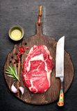 Raw Ribeye steak. With rosemary, garlic and olive oil on a wooden board Stock Image