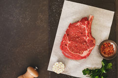 Raw ribeye steak ready for roasting on baking paper Stock Image