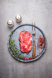 Raw Ribeye Steak with spices and meat fork on gray stone plate Stock Images