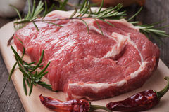 Raw ribeye steak. On wooden board with chili peppers and rosemary Stock Photography