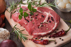 Raw ribeye steak. On wooden board with peppercorn and rosemary Royalty Free Stock Images