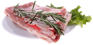 Raw ribs with rosemary. Plate with raw ribs with lettuce and rosemary. Isolated on white background stock image