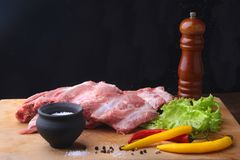 Raw Ribs on a rustic cutting board with salt, pepper and grinder for spices . Black Background for copy space. Top View. Raw Ribs on a rustic cutting board with Royalty Free Stock Photography