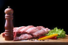Raw Ribs on a rustic cutting board with salt, pepper and grinder for spices . Black Background for copy space. Top View. Raw Ribs on a rustic cutting board with Stock Image