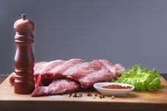 Raw Ribs on a rustic cutting board with salt, pepper and grinder for spices . Black Background for copy space. Top View. Raw Ribs on a rustic cutting board with Royalty Free Stock Photo