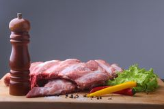 Raw Ribs on a rustic cutting board with salt, pepper and grinder for spices . Black Background for copy space. Top View. Raw Ribs on a rustic cutting board with Royalty Free Stock Image