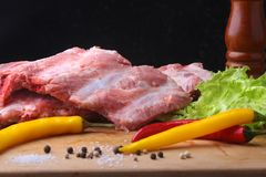 Raw Ribs on a rustic cutting board with salt, pepper and grinder for spices . Black Background for copy space. Top View. Raw Ribs on a rustic cutting board with Stock Images
