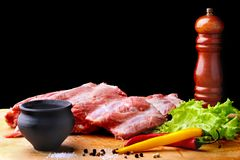 Raw Ribs on a rustic cutting board with salt, pepper and grinder for spices . Black Background for copy space. Top View. Raw Ribs on a rustic cutting board with Royalty Free Stock Photos