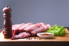 Raw Ribs on a rustic cutting board with salt, pepper and grinder for spices . Black Background for copy space. Top View. Raw Ribs on a rustic cutting board with Stock Photography
