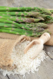 Raw rice and asparagus. Raw rice and green fresh asparagus on sack background Royalty Free Stock Photo