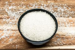Raw rice in a black bowl on wooden background. royalty free stock image