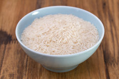 Raw rice on blue bowl Stock Images