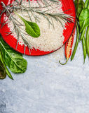 Raw Rice, fresh  delicious vegetables and ingredients for cooking on gray wooden background, top view Royalty Free Stock Image