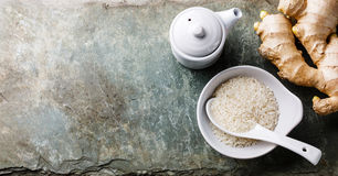 Raw rice, ginger root and soy sauce on stone background Royalty Free Stock Photography