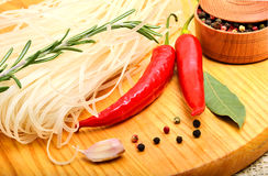 Raw rice noodles with chili pepper, rosemary twig, bay leaf, gar Stock Photo