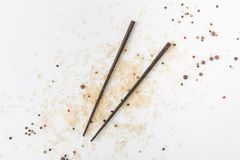 Raw rice and spices spilled on white surface with chopsticks royalty free stock image