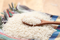Raw rice. In spoon on napkin and wood background Royalty Free Stock Photo