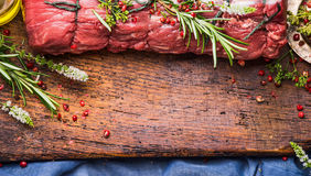Raw roast beef  with herbs and spices tied with a rope on wooden background, top view Royalty Free Stock Images