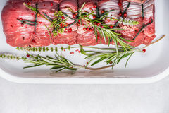 Raw roastbeef with fresh green herbs and spices marinated on light background Stock Photography