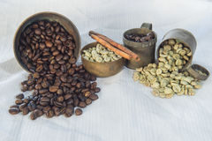 Raw and roasted coffee beans with brass cup on white table linen Royalty Free Stock Images
