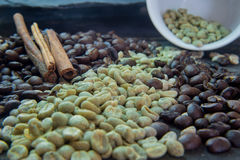 Raw and roasted coffee beans in brass cup and wicked container Royalty Free Stock Photo