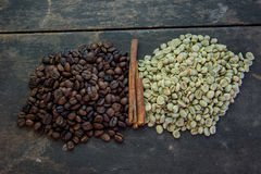 Raw and roasted coffee beans on wood table Royalty Free Stock Images