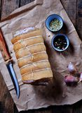 Raw roll of marinated pork belly with fennel seeds, dried basil, rosemary on a wooden table. Stock Photos